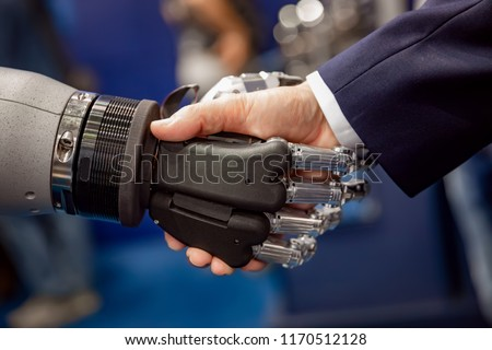 Hand of a businessman shaking hands with a droid robot. The concept of human interaction with artificial intelligence. #1170512128