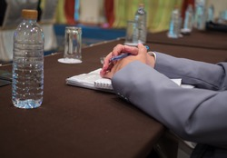 Hand of a businessman sitting in a meeting room holding hands.