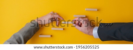 Hand of a businessman supporting a step in conceptual stairway for his female partner to walk her fingers upwards. Wide view image over yellow background. Foto stock ©