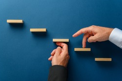 Hand of a businessman supporting wooden steps for his partner to walk his fingers upwards in a conceptual image of business partnership. Over blue background.