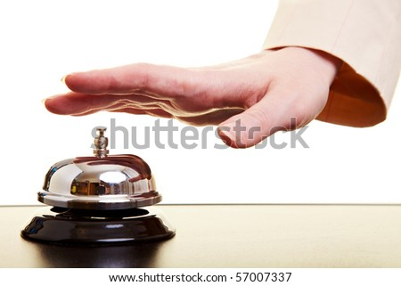 Hand of a businesswoman using a hotel bell