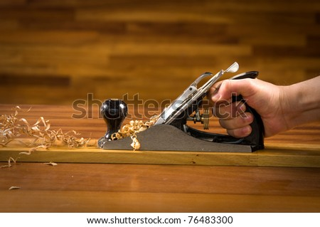 Hand of a carpenter using wood planer