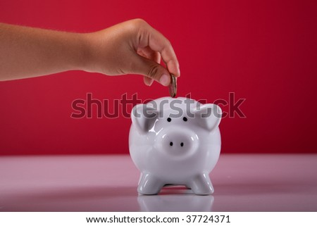 hand of a child saving some money on his piggy bank