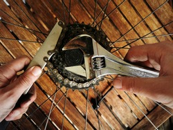 Hand of a craftsman manipulating a bicycle wheel for mending, maintenance and repair of a mountain bike sprocket. Using a chain whip and wrench. Wooden workbench in background.