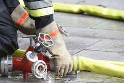 Hand of a fireman connecting a firehose to an outlet.