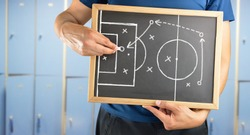 hand of a football coach drawing a tactics of soccer game  with white chalk on blackboard at changing room