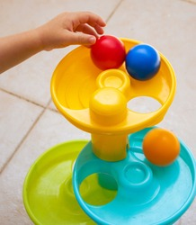 Hand of a girl playing with some colored balls in a plastic tower of bright colors.