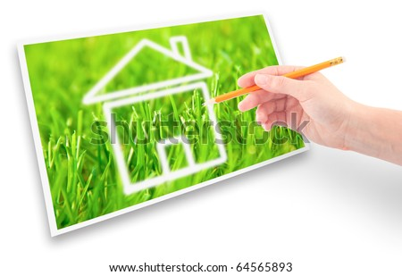 Hand of a girl with a pencil drawing a house of dream against the green grass.