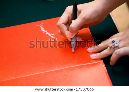 hand of a guest holding a pen writing on a red chinese wedding guests book