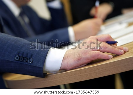 Hand of a male executive holding a fountain pen during a meeting or discussion. Decision making. Filling out documents, endorsement and signing. Close-up Stock photo ©