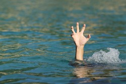 Hand of a man drowning in the sea trying to float