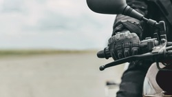 Hand of a man in protective motorcycle gloves holds a black motorcycle, close up