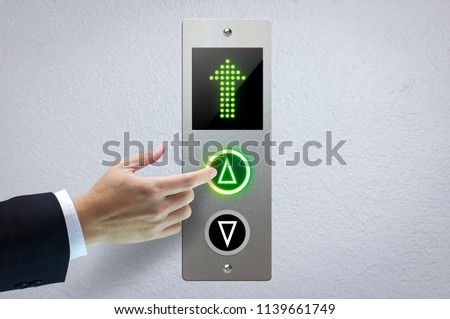 Hand of a man pressing the elevator button for next levels up in concept of more advance to a success.