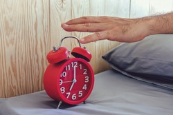 Hand of a man turn off alarm clock at morning