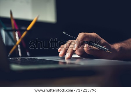 Hand of a man using laptop computer working overtime at his desk in the office late at night