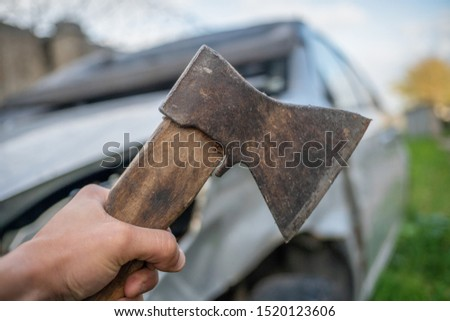 Hand of a man with an axe close - up on the background of a broken car