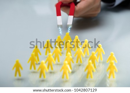 Hand Of A Person Attracting Group Of Yellow Figurines With Magnet On Reflective Desk #1042807129