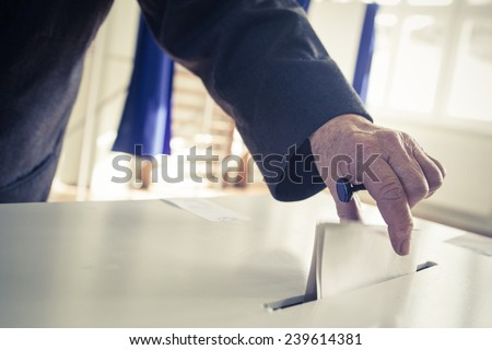Shutterstock Hand of a person casting a ballot at a polling station during voting.