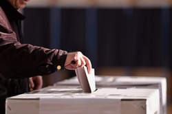 Hand of a person casting a vote into the ballot box during elections