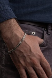 hand of a person in the pocket of his pants, uses a silver bracelet on his wrist, details of the textures