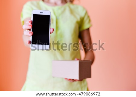Hand of a person with mobile phone and box on background. Delivery service application on smartphone. Close up image #479086972