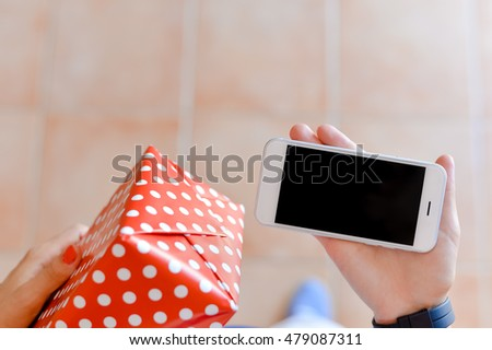 Hand of a person with mobile phone and box on background. Delivery service application on smartphone. Close up image, top view #479087311