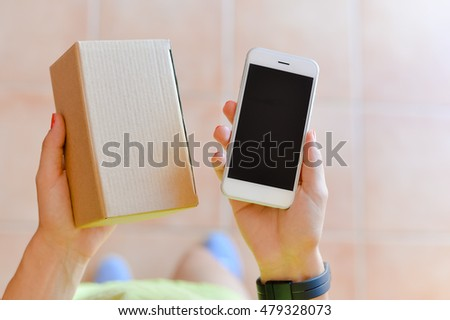 Hand of a person with mobile phone and box on background. Delivery service application on smartphone. Close up image #479328073