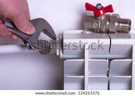 hand of a plumber  and radiator