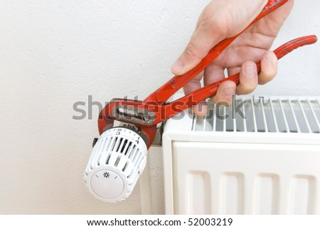 hand of a plumber with pliers and radiator