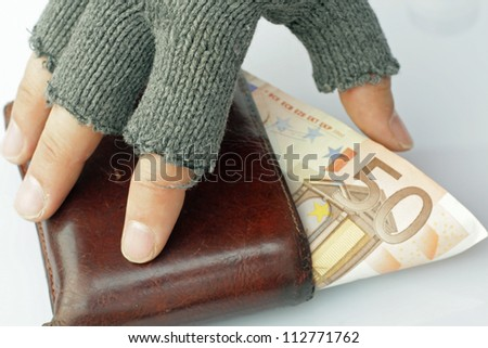 hand of a poor man who steals a banknote from wallet