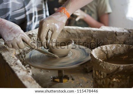 Hand of a potter shaping a clay pot on a pottery wheel with a spatula.