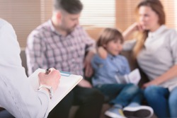 Hand of a professional family psychotherapist writing notes in front of a couple with a child in a blurred background during a consultation