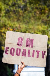 Hand of a protester holding a banner calling for gender equality on March 8, International Women's Day. Feminism, demonstrations, protest, women's rights.