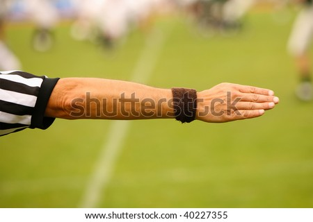 Hand of a referee showing to the right