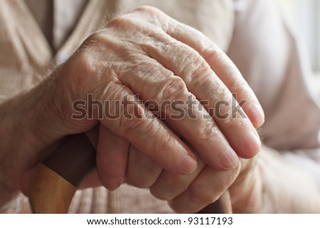 Hand of a senior man with a  cane