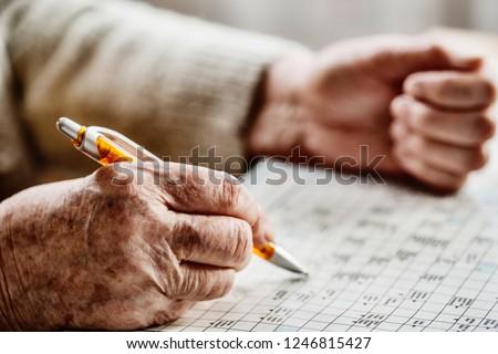 hand of a senior woman , sudoku, crossword Foto stock ©