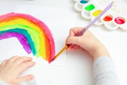 Hand of a small child paints a rainbow by watercolor with a brush.