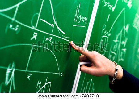 Hand of a student pointing at green chalk board - stock photo