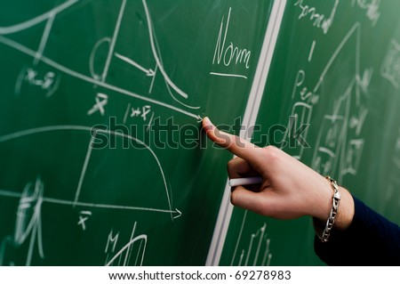 Hand of a student pointing at green chalkboard with normal distribution on it