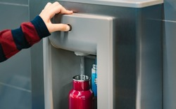 Hand of a traveler pressed the button of drinking water filling station at the Airport, Refill, Reusable bottle.  Eco friendly, Environmental awareness, Clean water, Zero waste, Plastic free july.