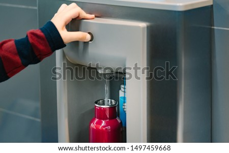 Hand of a traveler pressed the button of drinking water filling station at the Airport, Refill water, Reusable bottle.  Eco friendly, Environmental awareness, No Plastic, Clean water, Zero waste.