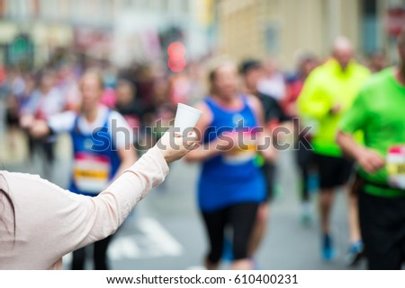 Hand of a volunteer giving a cup of water at a refreshment point in a marathon race to runners. #610400231