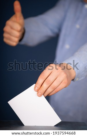 Hand of a voter putting vote in the ballot box. Election concept. Foto d'archivio ©