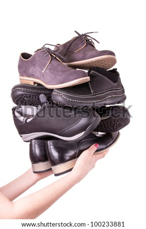 Hand of a woman holding shoes for men