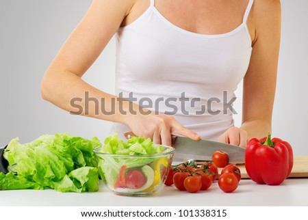 hand of a woman housewife preparing dinner, vegetables: tomatoes, peppers, lettuce on a cutting board in kitchen