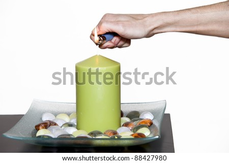 hand of a woman lighting a large candle with a lighter
