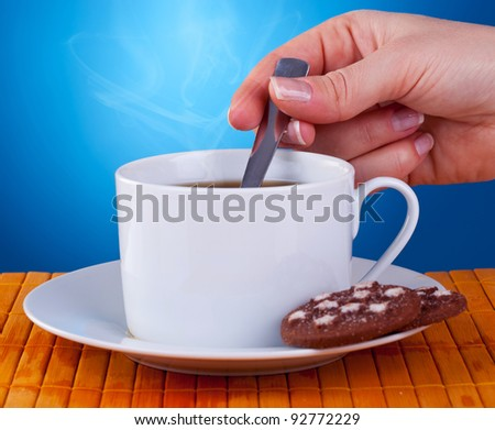 hand of a woman stiring in a fresh cup of coffee on blue background.