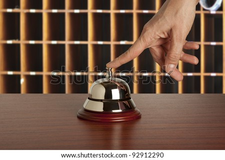 Hand of a woman using a hotel bell