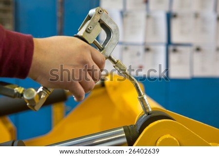 hand of a workman greasing the grease nipple of a hydraulic cylinder
