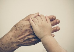hand of a young baby touching old hand of the elderly